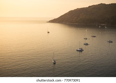 Sailing boats in the bay at sunset, view from above, mountain in the background. Bay with white yatch boat at Windmill viewpoint and Nai Harn Beach, Phuket, Thailand.