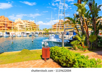 Sailing Boats in beautiful Sotogrande marina with colorful apartments and palm trees on shore, Costa del Sol, Spain