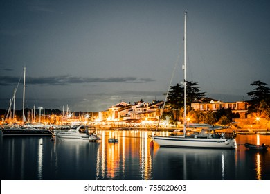 sailing boats by night in the haven of novigrad with lights in the background