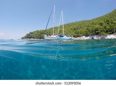 Sailing boats in calm waters in Skopelos island in Greece.