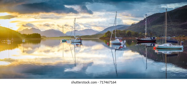 Sailing boats in colorful sunset reflections on Loch Leven, panorama from Glencoe, Scotland