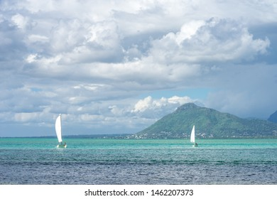Sailing boats float in the ocean against the backdrop of picturesque mountains and snow-white clouds. Mauritius Island, Indian Ocean