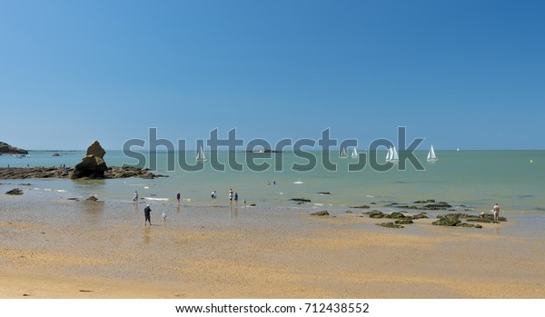 Sailing boats glide by on a hot summer day at a South Brittany beach in the Gulf of Morbihan,