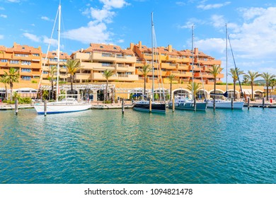 Sailing boats mooring in beautiful Sotogrande marina with colorful houses, Costa del Sol, Spain