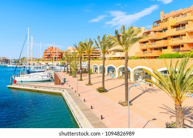 Sailing boats mooring in beautiful Sotogrande marina with colorful houses and palm trees on coastal promenade, Costa del Sol, Spain