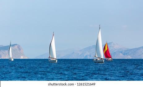 Sailing boats participate in yachting regatta.