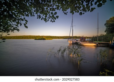 Sailing boats and a small pier on the shore of the large Jezioro Ostrowieckie in Pojezierze Zninskie in summer, Poland
