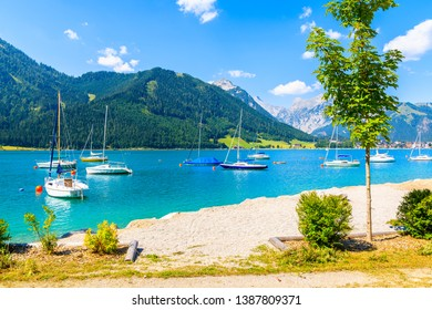 Sailing boats and view of beach near Pertisau town at beautiful Achensee lake on sunny summer day, Tirol, Austria