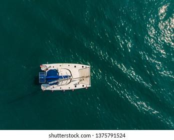Sailing catamaran in the bay, shooting from air