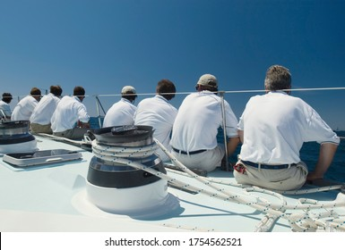 Sailing crew sitting on side of yacht on ocean back view