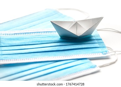 Sailing during pandemic crisis. Surgical mask with white paper ship on white background.