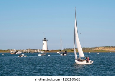 Sailing in Edgartown Harbor by Edgartown lighthouse on Martha's Vineyard island on a warm summer day in Massachusetts. It is one of the largest islands in New England.