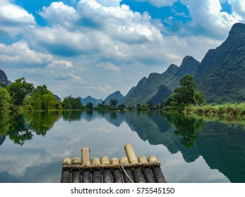 Sailing the Lijiang river by bamboo raft with the karst mountains of the Guilin countryside on the background