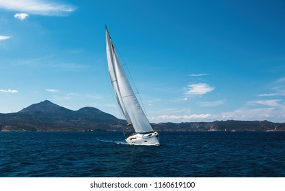 Sailing luxury yacht with white sails glides through the waves in the Sea.