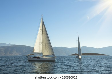 Sailing. Luxury yachts in the sea near the Greek Islands in the rays of the rising sun.