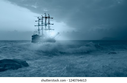 Sailing old ship in storm sea against amazing sunset