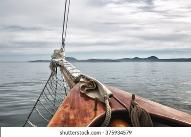 Sailing on a big vintage wooden schooner in the San Juan Islands, Washington State, USA. Close up view of the front of the boat. Mt. Rainier in the distance. Copy space.