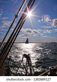 Sailing on Southampton Water, heading North West towards the Hamble, looking South West in the early evening into the setting sun (contre-jour), with another yacht in the distance.