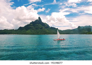 Sailing  over the turquoise-color lagoon , with the Otemanu mountain behind the scene .
