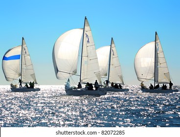 Sailing regatta in Greece: Four back-lighted boats with spinnakers open
