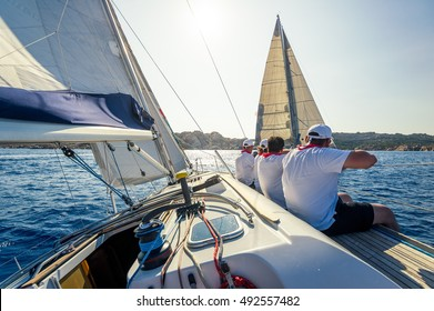 Sailing regatta on charter cruising boats. View from the cockpit to the crew sitting on the deck. Sardinia, Italy,