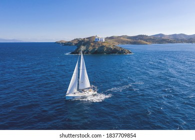 Sailing. Sailboat with white sails, rippled sea background, Lighthouse on a cape. Greece, Kea Tzia island. Summer holidays in Aegean sea. Aerial drone view