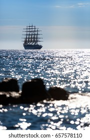 Sailing ship with five masts leaves at sunset in the open sea.