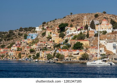 sailing ship in front of the skyline of Symi in Greece