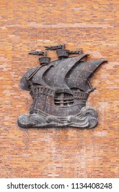 Sailing ship made of metal, on a wall with red bricks