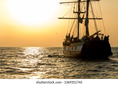 Sailing ship on the Aegean Sea at sunset. Three masts sailing boat cruising with tourists in Santorini, Greece.