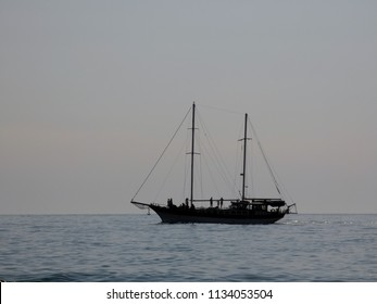Sailing ship with two masts moving in the water. Sea surface with small waves at the front. Some people on the boat. Cloudy summer day somewhere near Sochi, Russia