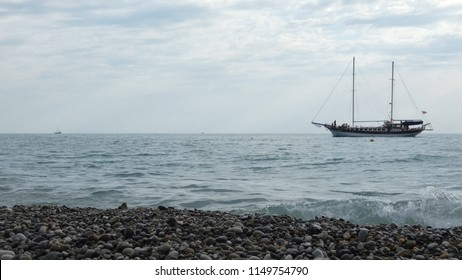 Sailing ship with two masts moving in the water. Sea coast with stones and pebbles at the front. Cloudy summer day somewhere near Sochi, Russia