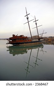 A sailing ship wrecked in a shallow lagoon
