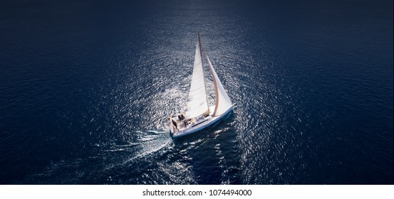 Sailing ship yachts with white sails at opened sea. Aerial - drone view to sailboat in windy condition.
