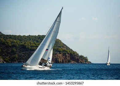 Sailing ship yachts with white sails in race the regatta in the open sea.