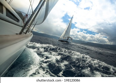 Sailing ship yachts with white sails in the sea in stormy weather.