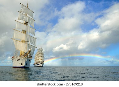 Sailing ships and a beautiful rainbow in the sea