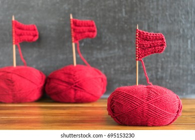 Sailing ships made from red yarn and knitting needles