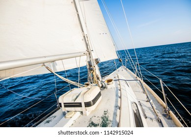 Sailing at sunrise. A view from the yacht's deck to the bow and sails. Baltic sea, Estonia