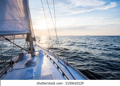 Sailing at sunset. A view from the yacht's deck to the bow and sails. Baltic sea, Latvia