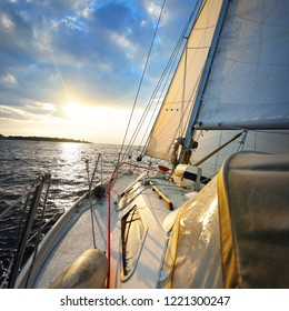 Sailing at sunset. A view from the yacht's deck to the bow and sails. Colorful evening sky over the Baltic sea