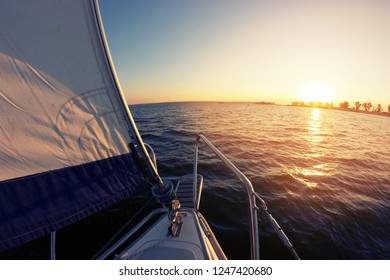 Sailing at sunset. A view from the yacht's deck to the bow and sails. Black sea