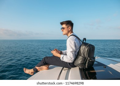 sailing, tourism, travel, business and people concept - handsome man on sail boat or yacht floating in sea over blue sea background.