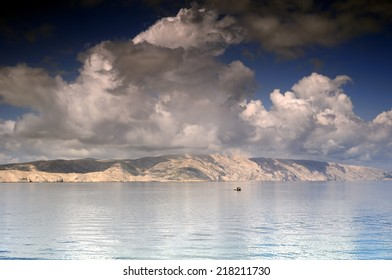 Sailing under the clouds, Small fishing boat on Adriatic sea, Croatia, in front of Krk island