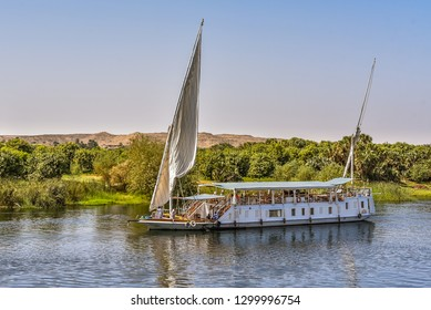 Sailing vessel on the river Nile close to the green shore and the desert, tourists relaxing on the deck, Nile, Egypt, October 23, 2018