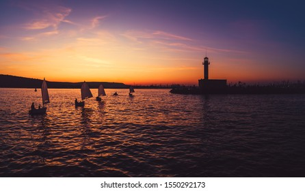 Sailing wind boats at sunset near lighthouse and sea port Varna, Bulgaria. Sport competition.