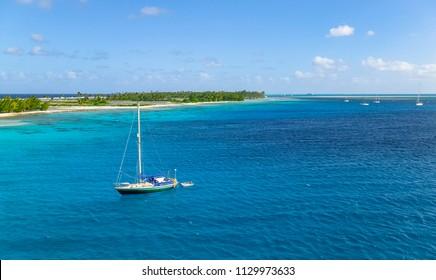 sailing yacht anchoring in the shallow, turquoise lagoon of Fakarava atoll, Tuamotus archipelago, French Polynesia, south pacific