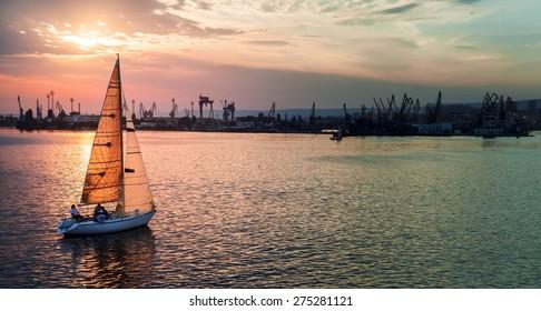 Sailing yacht enters Varna harbor at the sunset. Black Sea, Bulgaria. Stylized photo with tonal correction photo filter