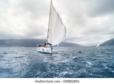 """Sailing yacht with flying. Tivat, Montenegro - 26 April, 2016. Regatta """"Russian stream"""" in God-Katorskaya bay of the Adriatic Sea off the coast of Montenegro."""
