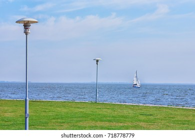 A sailing yacht goes along the shore